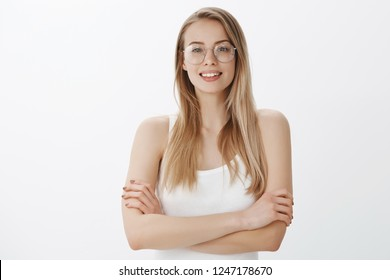 Confident and ambitious woman dreaming become director of company ready to work hard and determined holding hands crossed on chest in self-assured pose, smiling assertive over gray wall