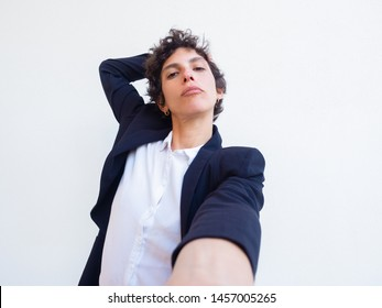 Confident androgynous young woman holding cell phone in hand and taking selfie. Self portrait of female professional in office suit. Poser concept