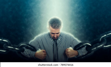 Confident and angry business man breaking chain. Business concept of liberation from credit slavery