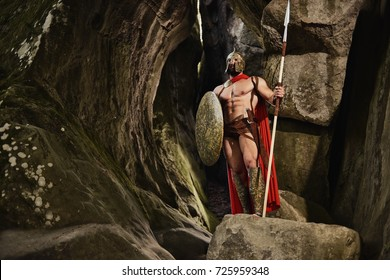 Confident anonymous man with muscular body holding weapon and shield while posign in gladiator outfit on rocks. Spartan.