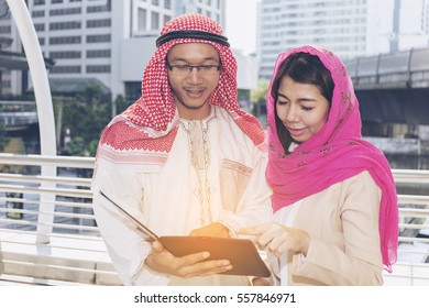Confident Arab business partners with laptop,notebook,and discussing work in downtown