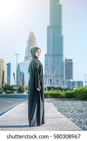 Confident Arab employee. Arab Business vumen in hijab is the street on the background of skyscrapers of Dubai. The woman is dressed in a black abaya