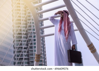 Confident Arabian Businessman standing and looking at city background for vision concept