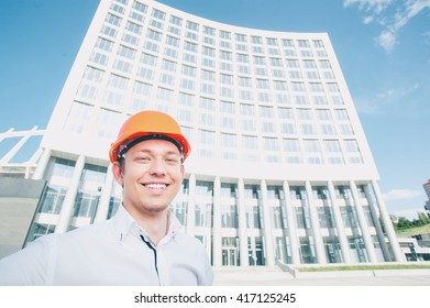Confident architect. Handsome smiling young man in hardhat standing outdoors against building structure