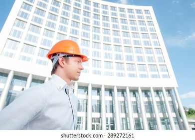 Confident architect. Handsome young man in hardhat standing outdoors  against building structure