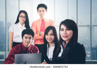 Confident Asian business people with laptop posing together in modern office