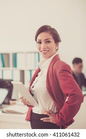 Confident Asian business woman with digital tablet smiling at camera