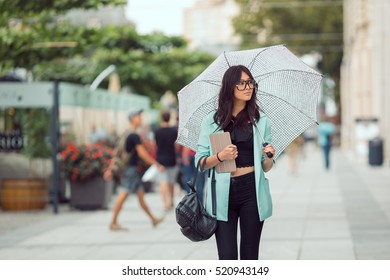 Confident asian business woman or hipster student with tablet walking in the city with umbrella. Mixed race Asian Chinese Caucasian elegant beautiful female model.