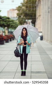 Confident asian business woman or hipster student with tablet standing in full length and looking at camera in the city with umbrella. Mixed race Asian Chinese Caucasian elegant beautiful female model