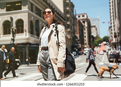 confident asian business woman in sunglasses standing on zebra crossing enjoy sunshine looking to blue sky. people walking dog and businessman in background. busy street road city urban san francisco