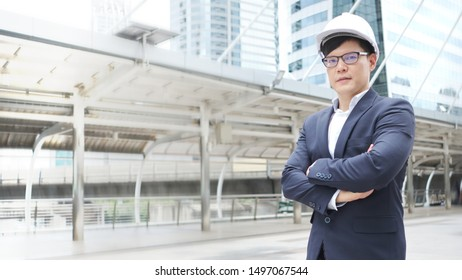 Confident Asian Businessman or Engineer is standing, his hand arms crossed and looking ahead with a vision that strives for success in a Business district full of tall buildings.