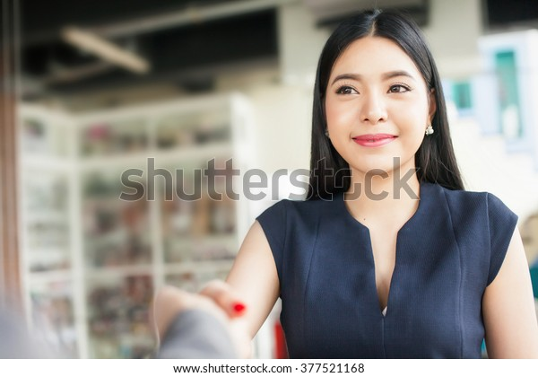 Confident Asian businesswoman smiling and shaking hands