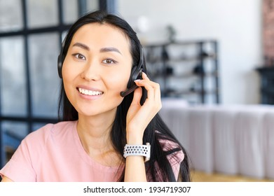 Confident asian female consultant with headset, looking at camera, talking with client, gives advice, dressed in ordinary clothes, best employee, has charming smile and perfect skin, natural makeup