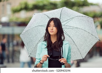 Confident asian girl city portrait. Serious woman outside with umbrella in casual business suite. Beautiful young mixed race Asian Caucasian woman.