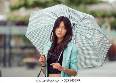 Confident asian girl city portrait. Serious woman outside with umbrella in casual business suite looking at camera. Beautiful young mixed race Asian Caucasian woman.