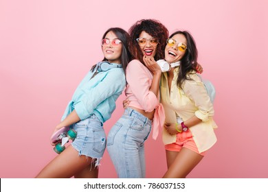 Confident asian girl in denim shorts posing with international female friends on indoor photoshoot. Beautiful ladies in bright clothes dancing with pleasure and laughing together.