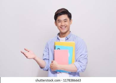 Confident asian handsome student holding books  gesture hand