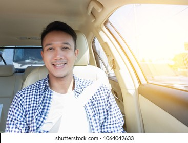 confident Asian man sitting in car seat beside the driver