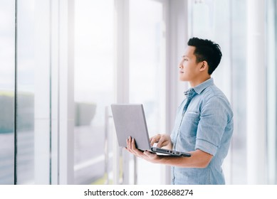 Confident Asian man using laptop with positive feeling for bright future in office building. business success concept.