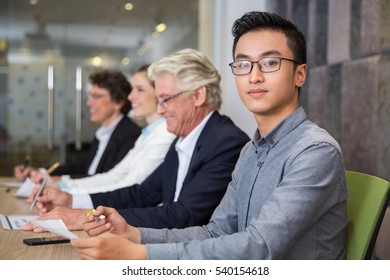 Confident Asian manager sitting at meeting
