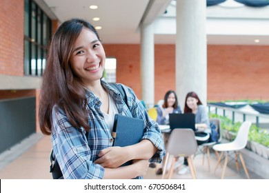 Confident Asian student holding books and smiling at camera ,education, campus, friendship and people concept