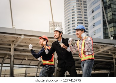 Confident asian team of construction workers and engineer in modern office