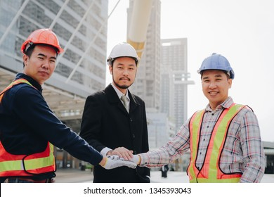 Confident asian team of construction workers and engineer join hands together to build successful projects with modern office background