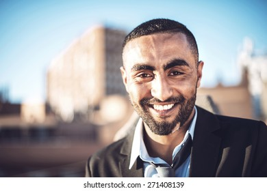 Confident attractive Arab businessman in urban environment