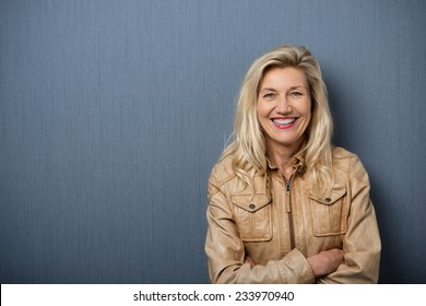 Confident attractive blond middle-aged woman with folded arms standing in front of a blank blackboard smiling happily at the camera with copyspace