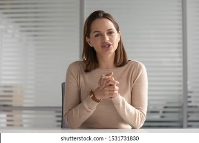 Confident attractive businesswoman looking at camera and talking, employee making video call, mentor coach tutor recording webinar, explaining online course, hr manager holding distance job interview