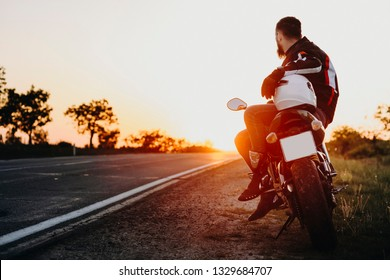 Confident attractive european biker sitting on his bike and looking at the sunset contemplating while resting in his traveling on the bike.