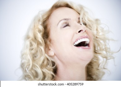 A confident and attractive middle-aged woman in white, laughing