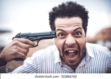 Confident attractive mulatto man with a gun