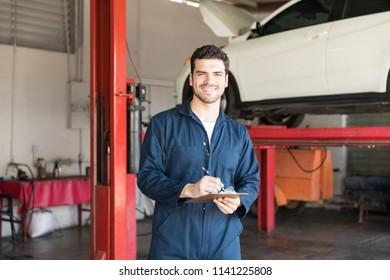 Confident auto repair expert preparing checklist for best service in garage
