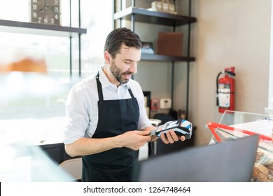 Confident baker inserting credit card in POS terminal at shop