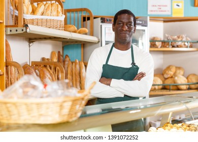 Confident baker standing in apron behind counter keeping arms crossed in small private bakery