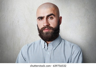 A confident bald male with thick black eyebrows and beard wearing checked shirt having gloomy expression posing against white background.People, fashion, lifestyle concept.