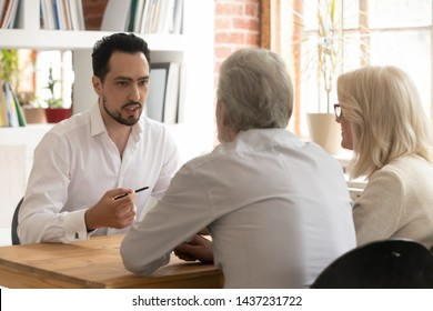 Confident bank manager lawyer agent consulting old senior couple clients at meeting, male financial advisor broker talking to elder family customers convincing to make insurance investment loan deal
