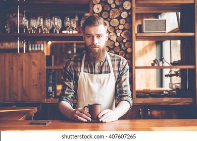 Confident barista. Young bearded man in apron looking at camera and holding coffee cup while standing at bar counter
