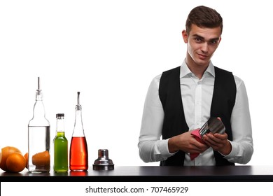 A confident barman in a classic suit cleaning a shaker for cocktails, isolated on a white background. A professional club bartender behind a bar counter. Colorful ingredients for beverages on a desk.