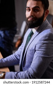 confident bearded brunette executive in suit posing at camera looking seriously, business people concept
