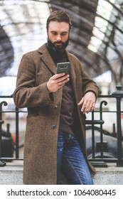 Confident bearded businessman standing with travel bag at the hall of railway station and texting message on his mobile phone