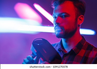 Confident bearded guy holding VR headset while standing in colorful glowing neon lights looking away.