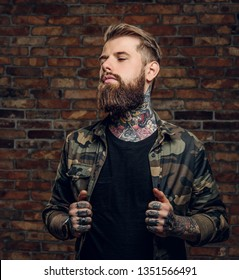 Confident bearded guy with tattoos on his hands and neck in the military shirt. Studio photo against a brick wall