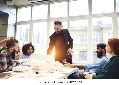 Confident bearded leader of working team making meeting with colleagues for discussing startup project, serious CEO using technology on conference talking about usage of digital gadget on meeting