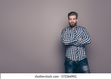 Confident bearded man with crossed hands isolated on gray background.