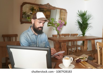 Confident bearded man sitting at table with laptop and headphones taking notes while having coffee with snack.