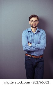 Confident bearded young man wearing brown leather belt, wristwatch, eyeglasses and blue jeans and casual shirt while standing with folded arms and leaning against a grey wall