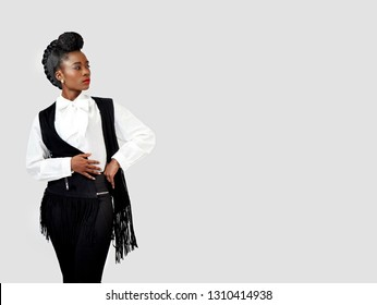 Confident beautiful African woman with her hand on her waist looking sideways wearing a stylish waistcoat with tussles