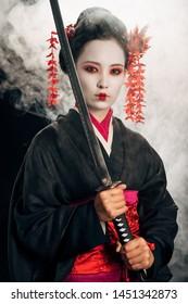 confident beautiful geisha in black kimono holding katana in smoke